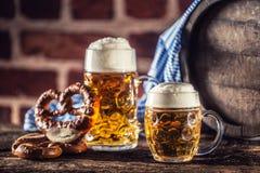 Großes und kleines Bier Oktoberfest mit hölzernem Fass der Brezel und blauer Tischdecke stockfoto