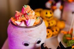 Großes verziertes Glas mit Kürbiseibischen auf dem Schokoriegel für die Feier von Halloween stockfoto