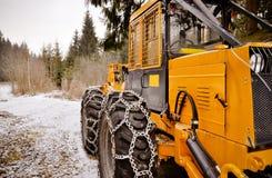 Großes Waldfahrzeug mit Schneeketten auf den Rädern Stockfotografie