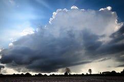 Großes Weiß und dunkle Wolken über Ackerland Stockbild