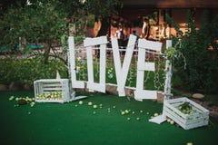 Großes weißes Liebeszeichen gemacht vom hölzernen Hochzeitsdekor Lizenzfreies Stockfoto