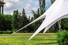 Großes weißes Zelt wird auf einen Rasen ausgedehnt Stockbild