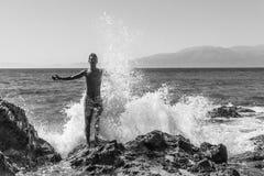 Großes Wellenspritzen auf dem Mann, der auf dem Strand steht lizenzfreie stockfotos