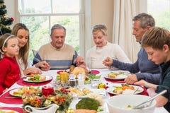 Großfamilie, die Anmut vor Weihnachtsabendessen sagt Stockbild