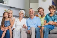 Großfamilie, die auf Couch im Wohnzimmer sitzt stockfotos