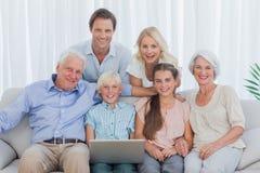 Großfamilie, die auf Couch sitzt Stockfotos