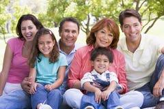 Großfamilie, die draußen lächeln sitzt Lizenzfreie Stockfotos