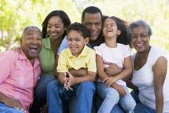 Großfamilie, die draußen lächeln sitzt Lizenzfreies Stockfoto