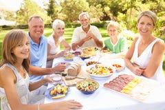 Großfamilie, die Mahlzeit im Garten genießt Lizenzfreies Stockfoto