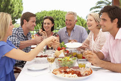 Großfamilie-Gruppe, die zusammen Mahlzeit im Freien genießt stockfotografie