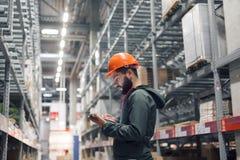 Großhandels-, logistisches, Leute- und Exportkonzept - Manager oder Aufsichtskraft mit Tablette am Lager lizenzfreie stockbilder