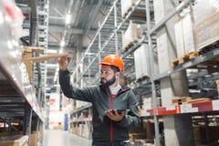 Großhandels-, logistisches, Leute- und Exportkonzept - Manager oder Aufsichtskraft mit Tablette am Lager lizenzfreie stockfotos