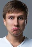 Großkopfkerl macht verrückte Gesichtsgefühle Stockfotografie