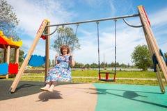 großmutter alte Frau, die ein Schwingen im Spielplatz reitet lizenzfreie stockfotos