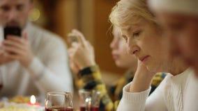 Großmutter, die das Internet auf Smartphone mit anderen Familienmitgliedern während Feiertag Weihnachtsessens, Abschluss oben an  stock video