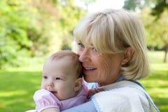 Großmutter, die draußen Enkelin hält Stockfoto