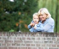 Großmutter, die draußen mit Baby lächelt Lizenzfreies Stockfoto