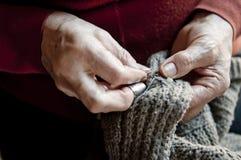 Großmutter, die eine Strickjacke näht Stockfoto