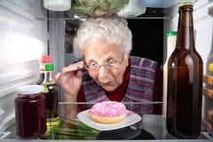 Großmutter, die einen Donut im Kühlschrank entdeckt stockfotografie