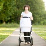 Großmutter, die einen Kinderwagen im Park drückt lizenzfreie stockfotos
