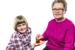 Großmutter, die Euromünze in Sparschwein der Enkelin einsetzt Stockbilder