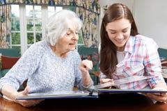Großmutter, die Foto-Album mit Jugendenkelin betrachtet stockbild