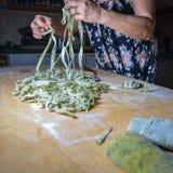 Großmutter, die frische Nessel gewürzte Bandnudeln vorbereitet Stockfotos
