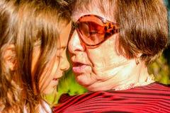 Großmutter, die ihre Enkelin hält Stockfoto