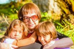 Großmutter, die ihre zwei Enkelinnen hält Stockbild
