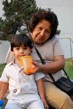 Großmutter, die ihrem Enkel Wasser gibt Lizenzfreie Stockfotos