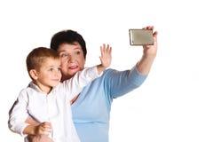 Großmutter, die ihren Enkel auf einem weißen Hintergrund umarmt und selfie macht Lizenzfreie Stockfotografie