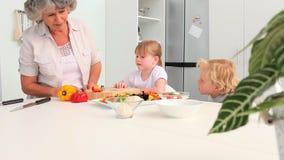 Großmutter, die mit ihren Enkelkindern kocht stock video