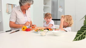 Großmutter, die mit ihren Enkelkindern kocht stock footage