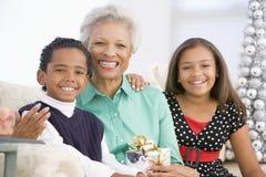 Großmutter, die mit ihren zwei Enkelkindern sitzt Stockfotografie