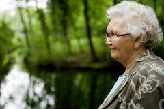 Großmutter, die nahe einem Strom steht Lizenzfreie Stockfotografie