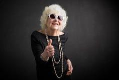 Großmutter, die sich Daumen zeigt stockfoto