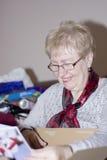 Großmutter, die sie Geschenke öffnet Lizenzfreies Stockbild