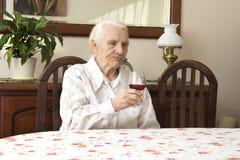 Großmutter, die am Tisch hält ein Glas Rotwein sitzt lizenzfreies stockfoto