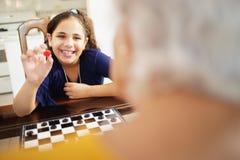 Großmutter, die zu Hause Kontrolleur-Brettspiel mit Enkelin spielt Lizenzfreie Stockfotos