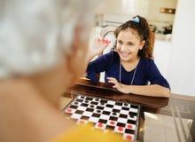 Großmutter, die zu Hause Kontrolleur-Brettspiel mit Enkelin spielt Lizenzfreies Stockbild