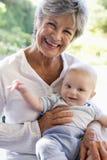Großmutter draußen auf Patio mit Schätzchen stockfotografie