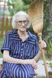 Großmutter mit dem Besen, der von der Hausarbeit stillsteht Stockbild