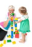 Großmutter mit den Enkelkindern, die mit Blöcken spielen Lizenzfreie Stockfotografie