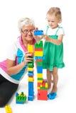 Großmutter mit den Enkelkindern, die mit Blöcken spielen Lizenzfreies Stockbild