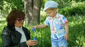 Großmutter mit einem Kinderstillstehenden Spielen im Park Blasen Sie Seifenblasen auf Im Freienerholung stock video footage