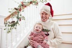 Großmutter mit Enkelin sitzt auf Treppe am Weihnachten Stockfotografie