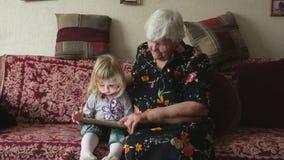 Großmutter mit todler Mädchen, das Bilder schaut stock footage