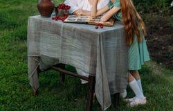 Großmutter sitzt am Tisch mit ihrer Enkelin, zeigt ihr ein altes Album mit Fotos ihrer Jugend ist auf dem Tisch ein Lehmvase lizenzfreie stockfotos