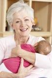 Großmutter-streichelnenkelin zu Hause Stockfotografie