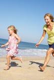 Großmutter und Enkelin, die entlang Strand laufen Stockfotos